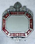 Espelho Veneziano em cristal espelhado, lapidado com detalhes em pintura vermelha no verso do cristal, pequenas faltas medindo 100 cm de altura por 59 cm de largura.