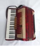 Acordeon Scandalli 80 baixos com terça de voz, sete registro no teclado e dois no baixo. Na cor vermelha, L 662/39, made in Italy, em perfeito estado de conservação e no estojo original medindo fechado 50 cm por 45 cm por 25 cm.