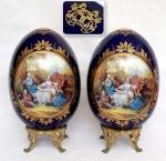 Par de ovos decorativos em porcelana Europeia azul cobalto com impressão de cena de sarau familiar em reserva com realces em ouro sobre base em metal, marcado Limoges na parte inferior, medida total de 25 cm de altura por 15 cm de diâmetro.