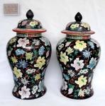 Par de antigas bilhas em porcelana Chinesa com tampas marcadas na base uma delas com antigo restauro na boca decoradas com flores e com fundo negro, medindo 40 cm de altura por 22 cm de diâmetro.