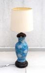Grande vaso em porcelana Oriental azul e branca medindo 50 cm de altura por 25 cm de diâmetro no bojo, adaptado para abajur com peanha e arremate superior em madeira torneada, medida total com a cúpula 109 cm de altura por 40 cm de diâmetro.