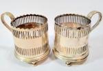 PRATA -  Elegante e antigo par de suporte para xícaras de café, em prata 900 contrastados, finamente cinzelados, apoiados sobre 3 pés. Med 7x8 cm. Peso total aproximadamente: 214 gramas.