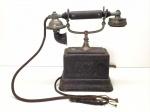 Antigo telefone de mesa em ferro. Med. 25x25x11 cm.
