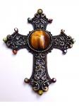 ARQBIJU. Pingente  crucifixo metálico fenestrado no tom ouro velho (medindo  8 cm x 6 cm) tendo ao centro pedra natural (olho de tigre) e extremidades com aplicação de strass cristal furta-cor sobre base no tom bordô.