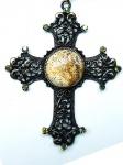 ARQBIJU. Pingente  crucifixo metálico fenestrado no tom ouro velho (medindo 08cm x 06cm) tendo ao centro pedra natural (jaspe) e extremidades com aplicação de strass cristal furta-cor sobre base no tom oliva.