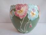 Cachepot em  cerâmica com borda trabalhada com flores  (apresenta quebrado e colado na borda), mede 20cm de diâmetro e  22cm de altura.