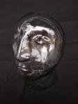 Escultura em vidro translúcido, representando cabeça, medindo 23cm de altura.