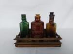 Tres vidros de pharmacia  com suporte em madeira com galeria.  ( falta  a tampa do verde e cor de ambar tem restauro)