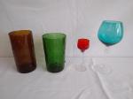 Quatro itens em vidros coloridos,  2 copos em vidro grosso lapidado, 1 taça para vinho com pé alto na cor azul e 1 taça para licor na vermelha.