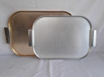 Duas bandeja em alumínio, no formato retangular com alças, sendo 1 prateada e a outra dourada,