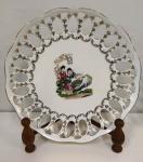 Belíssimo prato vazado com representação de queixas e ornamentos dourados. Marca POLOVI - Mede: 27 cm(Am)