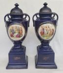 Empire Porcelain Company, par de ânforas em porcelana Inglesa pintura azul cobalto com cenas românticas em reserva medindo 42 cm de altura por 14 cm por 14 cm na base, interior preenchido com areia e tampas coladas, apresenta desgastes na douração.