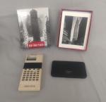 """Agenda eletrônica, marca """"Sharp"""", 64 KB medindo 13,5 cm x 8,5 cm, caixa com 16 Cards """"The Metropolitan Museum Of Art"""" com 18 envelopes e uma calculadora da marca """"Canon Pocket Printer"""", modelo TP-8 medindo 17,5 cm x 7 cm. Eletrônicos não testados e sem garantia de funcionamento."""