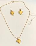 """Conjunto em metal banhado a ouro da grife """"Pierre Cardin"""" com um colar e um pingente em forma de coração medindo 20 cm de comprimento (colar) e 1,5 cm (pingente) e um par de brincos em forma de coração medindo 1,5 cm."""