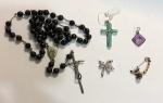 Terço em metal prateado com miçangas preta medindo 45 cm de comprimento e quatro pingentes diversos medindo 3,5 cm (maior) e 2,5 cm (menor).