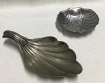 Dupla de saboneteiras em formato de concha, sendo 1 espessurada a prata (necessita limpeza) e outra em aço inox. Marcas do tempo. No estado.