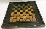 Jogo de damas com tabuleiro e peças em pedra sabão nas cores verde e bege (faltam 2 pedras). Marcas do tempo. No estado.