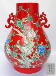 Grande e muito pesado vaso em porcelana chinesa no formato HU, decorado com belas folhagens e pássaros em policromia sobre fundo vermelho coral. No verso texto com poema. Assinado. Marca apócrifa QIANLONG no fundo. Período Republicano (1912-1949). Med. 52 x 40 cm. Uma das alças com restauro.