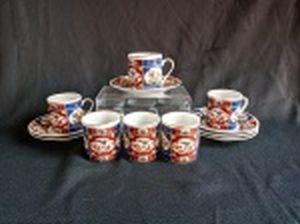 Seis xícaras e pires para café em porcelana branca, decoração policromada em azul e vermelho no estilo chinês, frisos prateados na borda da xícara. Alt. total 7cm.