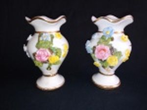 Par de vasos de porcelana em miniatura, aplicado com flores policromadas moldadas em alto relevo, borda em babado, frisos dourados. Alts. 11cm.
