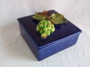 Caixa quadrada em cerâmica vitrificada de azul cobalto, aplicada na tampa com cacho de uva e folhas de parreira  em alto relevo.  Bicado na folha. 8 x 13 x 13cm.