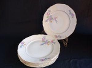 Seis pratos rasos em porcelana polonesa decorada com flores em policromia e frisos à ouro. Marca da Manufatura Koenigszelt. Íntegros. Diam. 25cm.