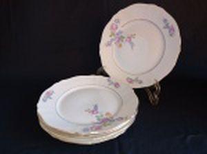 Cinco pratos rasos em porcelana polonesa decorada com flores em policromia e frisos à ouro. Marca da Manufatura Koenigszelt. Íntegros. Diam. 25cm.