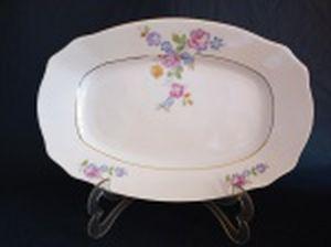 Travessa em porcelana polonesa decorada com flores em policromia e frisos à ouro. Marca da Manufatura Koenigszelt. Íntegra. 32,5 x 21,5cm.