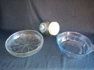 Três peças em vidro translúcido: a) Saladeira decorada com folhas em relevo. Alt. 6 x diam. 24cm. b) Bowl com alças decorado com faixa de arabescos. Alt. 8 x diam. 23cm. c) Baleiro chanfrado, tampa forrada em tecido bege. Alt. 16cm.