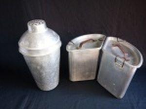 Três peças em alumínio; 2 marmitas (parte de um jogo de 3) e grande coqueteleira (falta a tampa). No estado. Alts. 17 e 28cm.
