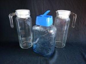 Três peças: a) Duas jarras para suco, vidro translúcido e oitavado, tampas plásticas. Alt. 24cm. b) Garrafa para água, vidro moldado com frutas, tampa plástica. Alt. 23cm.