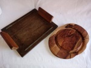 Duas peças em madeira: a) Bandeja retangular. Selo no fundo da loja Merci... 35 x 28cm. b) Tábua para queijo (falta a tampa). 29 x 22cm.
