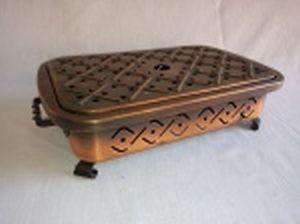 Rechaud em chapa de cobre, alças e pés em ferro torcido, 2 queimadores para vela, chapa e laterais vazadas. 8 x 32 x 18cm.
