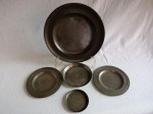 Cinco peças de estanho: sousplat, dois pratinhos, salva e porta-copos. Diferentes manufaturas. Diâm. maior 30cm, diâm. menor 10cm.