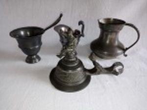 Quatro peças em estanho: 2 jarrinhas para molhos, molheira com colher e tampa de tankard ornamentada com soldado e pássaro. Maior 10cm, menor 7cm.