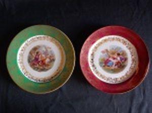 BAVARIA - Dois pratinhos decorativos em porcelana bávara, borda com cinturão azul e vermelho ricamente ornamentada por decoração floral filetada a ouro, centro aplicado com cenas galantes em policromia. Marcados no fundo. 18cm.