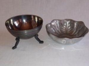 Duas petisqueiras em estanho, sendo uma alta com 3 pés, manufatura Jormeb, 8 x 12cm; e uma moldada na forma de folhagens, 5 x 14cm.