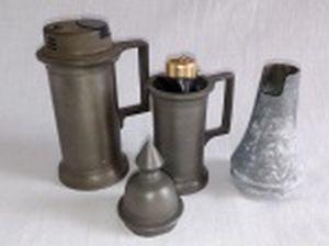 Três suportes para isqueiro em estanho, formatos diversos, um acompanhando isqueiro. Apresentam desgastes e marcas do tempo. Alt. 12, 11 e e 9cm.
