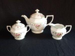 SCHMIDT - Três peças para serviço de café em porcelana nacional branca: bule, açucareiro e leiteira. Decoração com arranjos florais lilás e frisos verdes. Apresenta leves craquelados na tampa do açucareiro. Marcados no fundo. Alts. 18, 12 e 9cm.