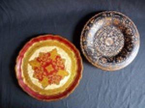 Dois pratos decorativos em madeira, sendo um ricamente policromado com vermelho e dourado, interior ornamentado com acantos e cinturão de folhas de louro, diâm. 23cm; e um com fundo preto decorado com fragmentos de placagem de madeira formando flores, diâm. 21cm.
