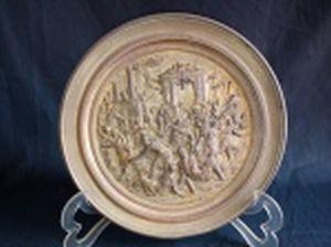 Placa decorativa redonda em metal aplicada no centro em alto relevo com cena da queda do Império Romano, representando o ataque dos visigodos às portas do Senado. Diâm. 22cm.