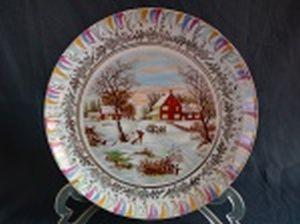 Prato decorativo em porcelana branca, borda e cinturão de folhagens filetados a ouro, centro aplicado com cena rural no inverno. Marca no fundo não identificada. Diâm. 25cm.