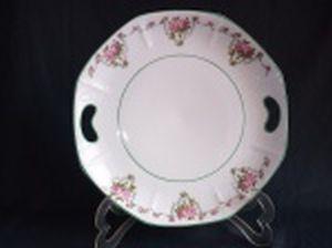 SCHMIDT - Prato com alças em porcelana nacional branca, borda e detalhes em friso verde, decoração policromada com guirlandas de rosas, formato sutilmente oitavado. Marcado no fundo. Diâm. 27cm.