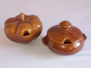 Duas farinheiras em porcelana marrom, uma na forma de moranga e uma lisa. Alt. 11 x diam. 15cm e Alt. 11 x diam. 13cm.
