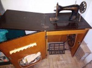 Máquina de costura manufatura Singer, gabinete de madeira. Uma das laterais descolando. Não testada e sem garantias. No estado. 78 x 54 x 42cm.