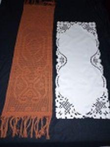 Dois caminhos de mesa, 1 com bordados e tecido branco e 1 em crochê marrom. 87 x 33 e 110 x 32cm.