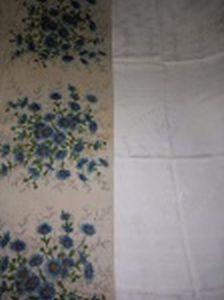Duas toalhas de mesa em tecido; 1 adamascada com flores 150 x 135cm e 1 estampada com flores azuis 160 x 135cm.