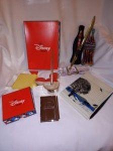 Diversos blocos de anotação com canetas, sendo uma em estojo de metal no formato de garrafa de Coca-Cola e outros da Disney.