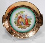 PORCELANA DP 541 - Refinado e grande prato para bolo em porcelana com farta douração decorada por cena bucólica em policromia. Mede 29 cm de diâmetro. OBS: Possui desgaste em alguns pontos da douração na parte exterior (por baixo) da borda.
