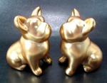 Decorativo par de cães em porcelana de tom ouro fosco medindo 9 cm de altura por 7,5 cm de comprimento cada.